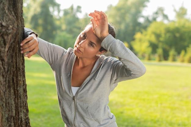 Middelgroot schot vermoeide vrouw dichtbij boom