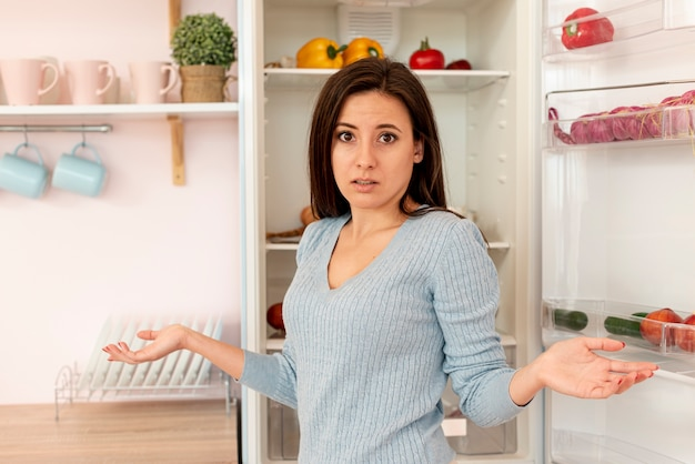 Middelgroot schot verwarde vrouw in de keuken