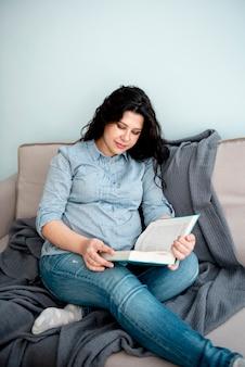 Middelgroot schot zwangere vrouw die een boek leest