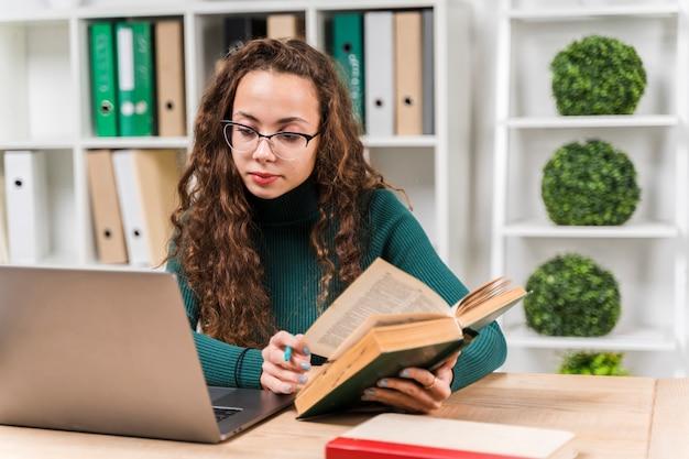 Middelgroot schotmeisje dat met woordenboek en laptop bestudeert
