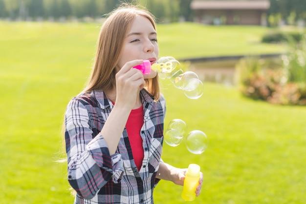 Middelgroot schotmeisje dat zeepbels maakt