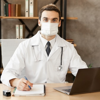 Middelgrote arts die binnenshuis masker draagt