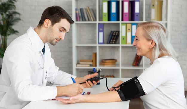Middelgrote arts die bloeddruk meet