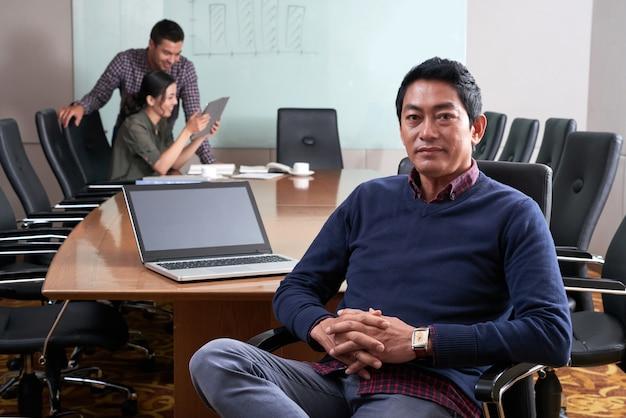Middelgrote close-up van de mens in vrijetijdskledingzitting bij de conferentielijst die camera bekijken