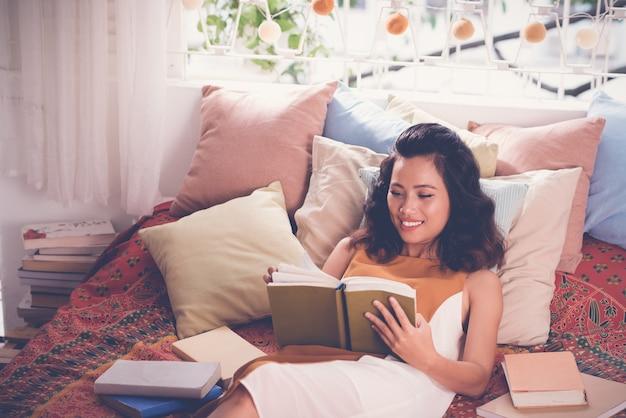 Middelgrote close-up van jonge vrouw die een boek in haar bed leest