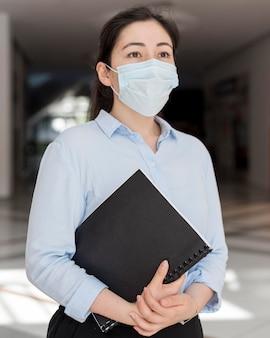 Middelgrote geschoten bedrijfsvrouw die masker draagt