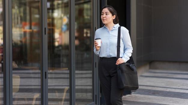 Middelgrote geschoten bedrijfsvrouw met koffie