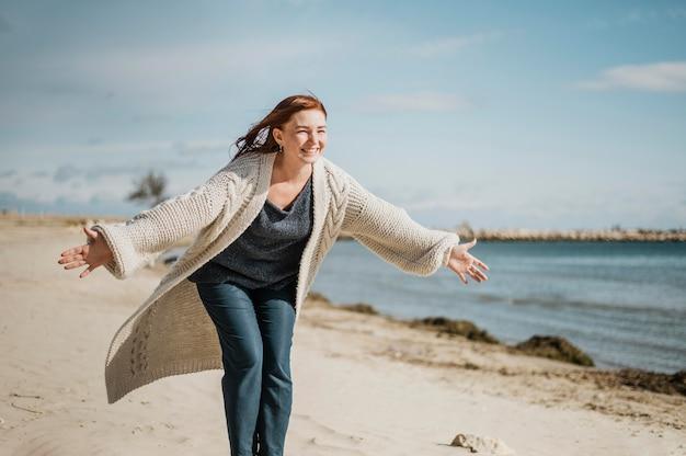 Middelgrote geschoten gelukkige vrouw bij strand