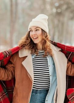 Middelgrote geschoten gelukkige vrouw met deken