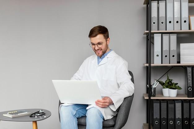 Middelgrote geschoten smileyarts die met laptop werkt