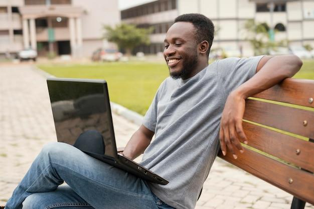 Middelgrote geschoten smileystudent met laptop