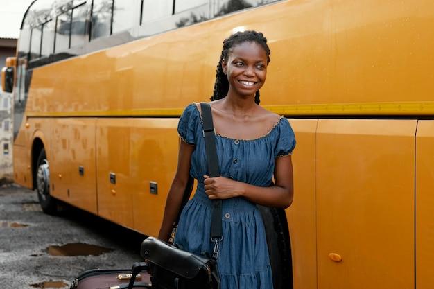 Middelgrote geschoten smileyvrouw dichtbij bus