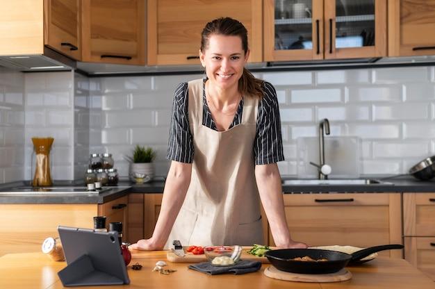 Middelgrote geschoten smileyvrouw in keuken