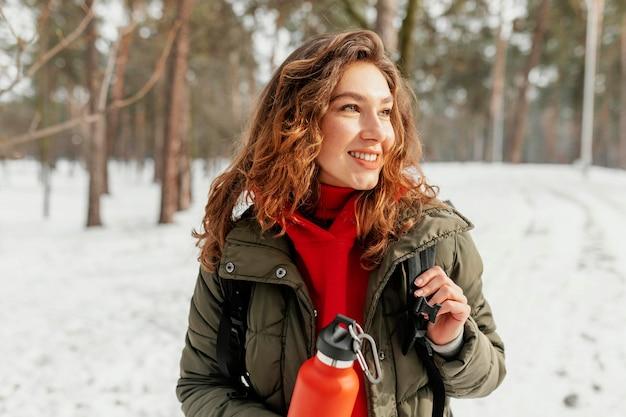 Middelgrote geschoten smileyvrouw in sneeuw