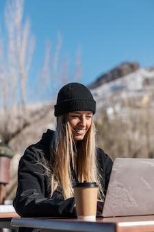 Middelgrote geschoten smileyvrouw met laptop