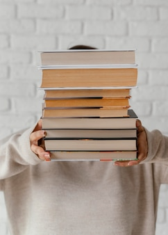 Middelgrote geschoten student met boekenstapel