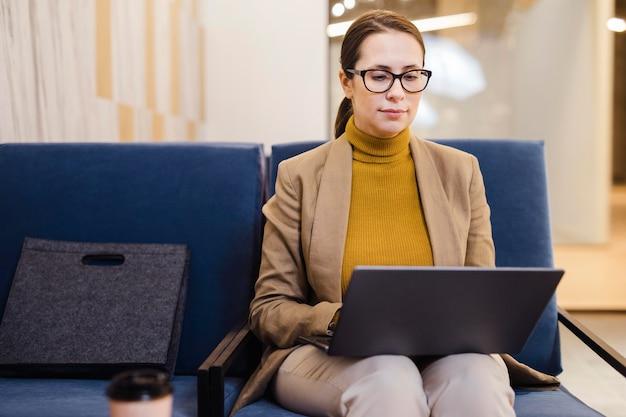 Middelgrote geschoten vrouw die aan laptop werkt