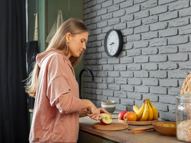 Middelgrote geschoten vrouw die appel snijdt