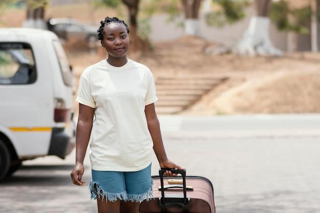 Middelgrote geschoten vrouw die bagage draagt