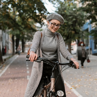 Middelgrote geschoten vrouw die de fiets berijdt