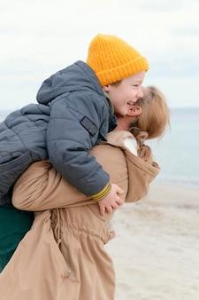 Middelgrote geschoten vrouw die gelukkige jongen houdt