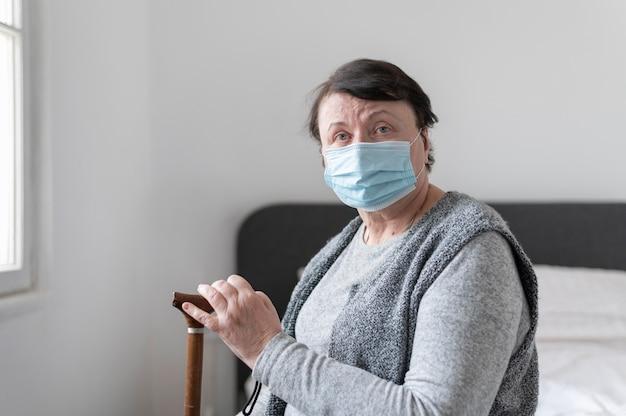 Middelgrote geschoten vrouw die gezichtsmasker draagt