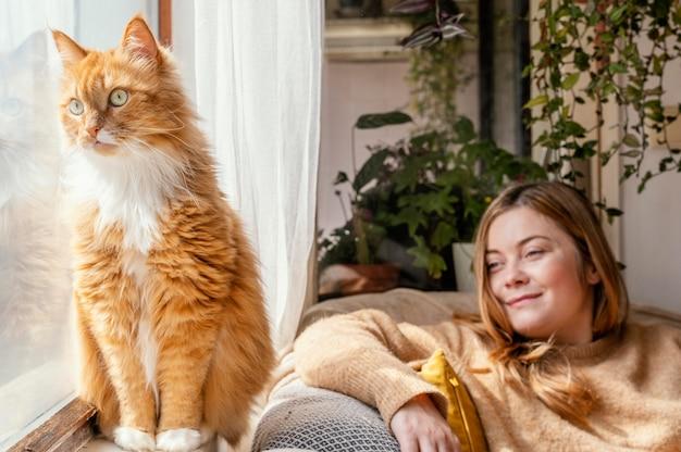 Middelgrote geschoten vrouw die kat bekijkt