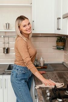 Middelgrote geschoten vrouw die met handdoek schoonmaakt