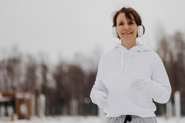 Middelgrote geschoten vrouw die met hoofdtelefoons loopt