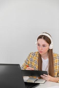 Middelgrote geschoten vrouw die met hoofdtelefoons werkt