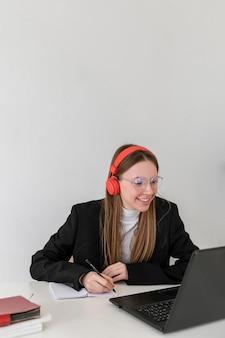 Middelgrote geschoten vrouw die met laptop werkt