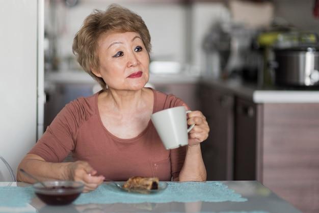 Middelgrote geschoten vrouw die ontbijt neemt