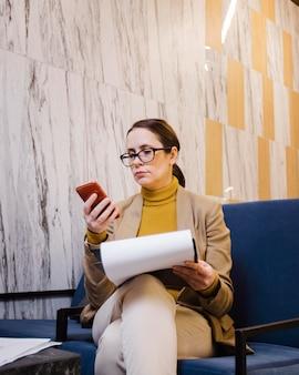 Middelgrote geschoten vrouw die telefoon bekijkt