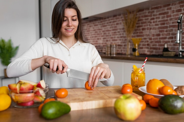 Middelgrote geschoten vrouw die tomaat snijdt