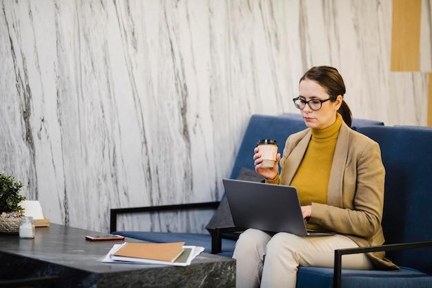 Middelgrote geschoten vrouw met laptop en kop