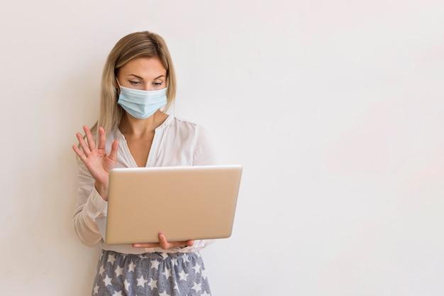 Middelgrote geschoten vrouw met masker en laptop
