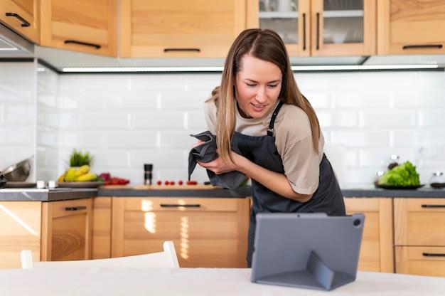 Middelgrote geschoten vrouw met tablet in keuken
