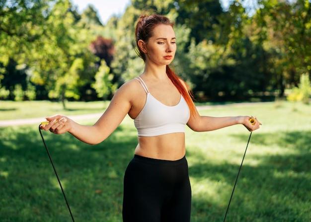 Middelgrote geschoten vrouw met touwtjespringen