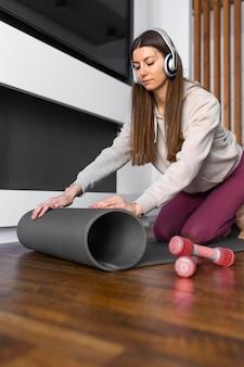 Middelgrote geschoten vrouw met yogamat