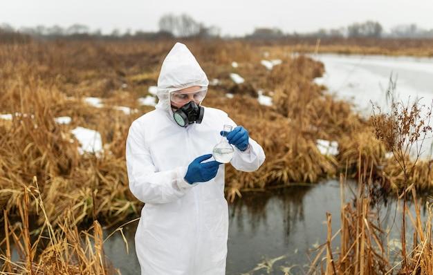Middelgrote geschoten wetenschapper die beschermend pak draagt