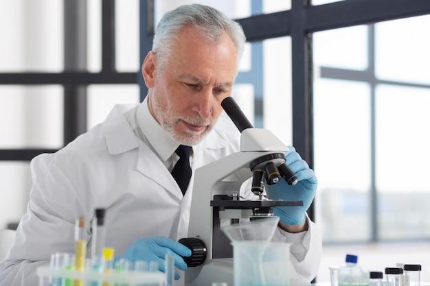 Middelgrote geschoten wetenschapper die door microscoop kijkt