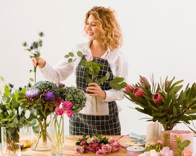 Middelgrote geschotene gelukkige bloemist die bloemen schikken