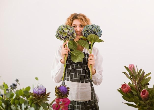 Middelgrote geschotene gelukkige bloemist die twee boeketten steunt