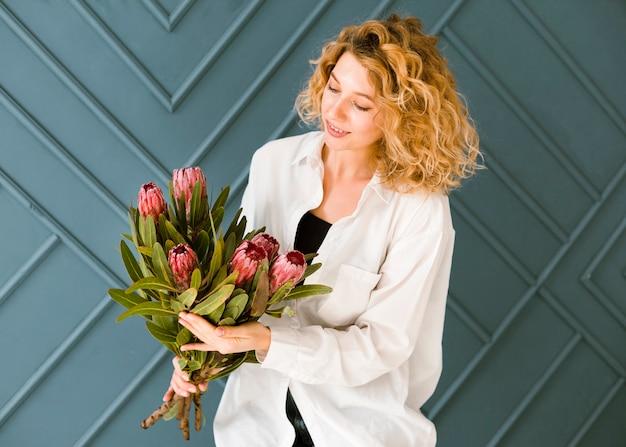 Middelgrote geschotene gelukkige vrouw die bloemen bekijken