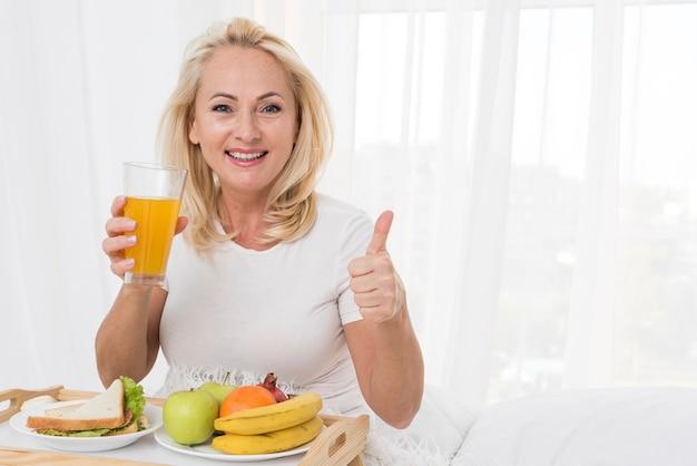 Middelgrote geschotene gelukkige vrouw met jus d'orange die goedkeuring toont