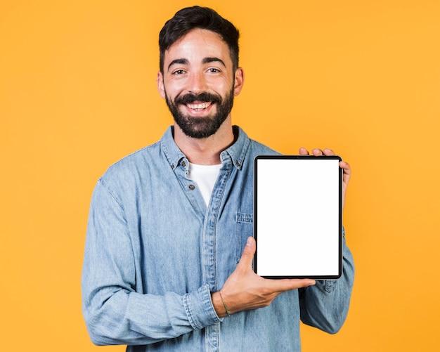 Middelgrote geschotene kerel die een tablet houdt