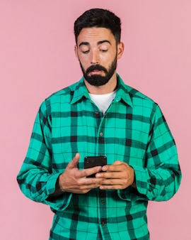 Middelgrote geschotene kerel die op de telefoon kijkt