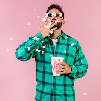 Middelgrote geschotene kerel die popcorn eet