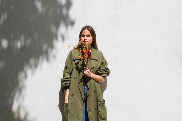 Middelgrote geschotene maniervrouw die een bos van peper houden