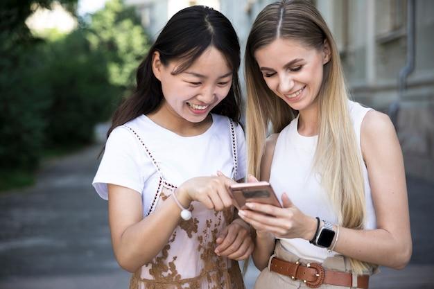 Middelgrote geschotene meisjes die bij telefoon glimlachen